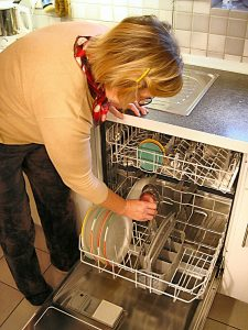 Eine Frau räumt Geschirr in eine Spülmaschine ein.